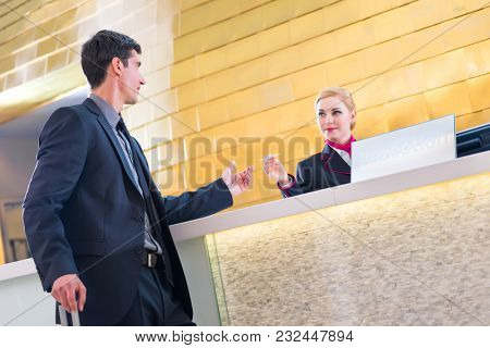 Man check-in at reception or front office of design hotel