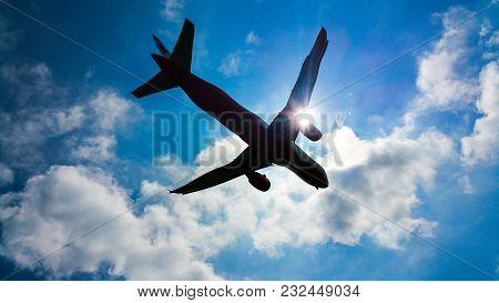 Airplaine Flying Under The Beautiful Clouds And Sun.