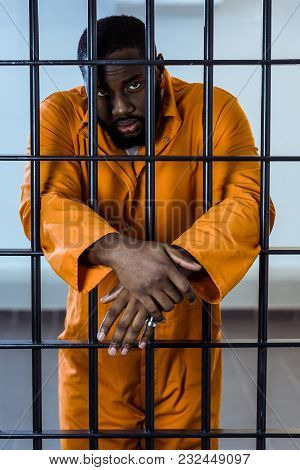 African American Prisoner In Uniform Standing Behind Prison Bars