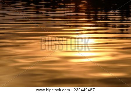 Golden Background Of Water Texture With Sun Reflection And Beautiful Soft Waves At Sunset