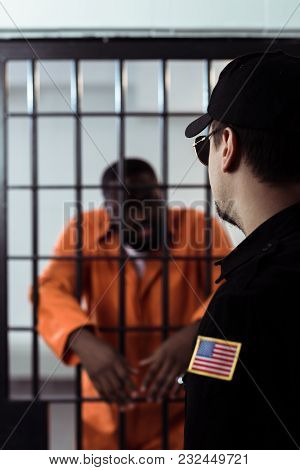 Security Guard Standing Near Prison Bars And Looking At African American Prisoner