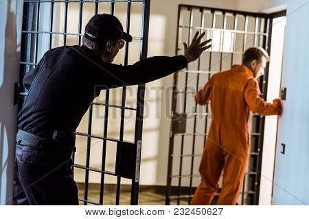 Security Guard Showing Stop Sign To Escaping Prisoner