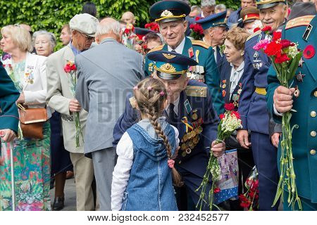 Kiev, Ukraine - May 9, 2016: Girl Gives Flowers To The Veterans Of The Great Patriotic War In The Pa