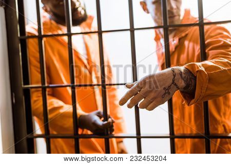 Multicultural Prisoners Standing Near Prison Bars In Prison Cell