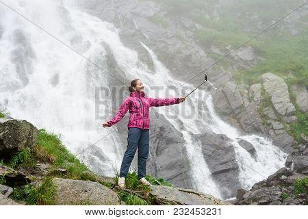 Pretty Young Woman Taking A Selfie In Front Of Big Powerful Waterfall Balea In Romanian Fagarash Mou