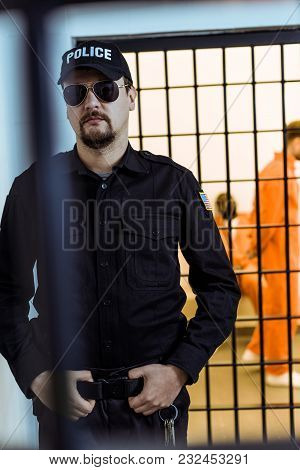Police Officer Standing Near Prison Cell With Multicultural Inmates