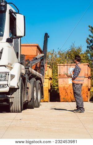 Worker on construction site unloading container for waste from truck using remote control