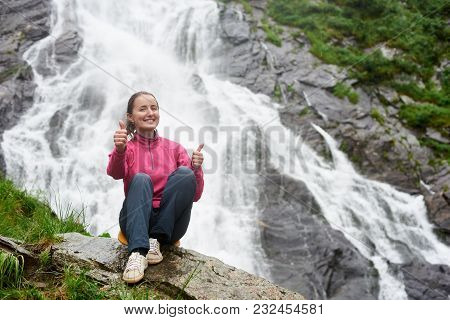 Smiling Young Attractive Woman Showing Thumbs Up While Sitting On Rock In Front Of Magnificent Balea