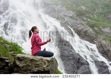 Female Yogini. Attractive Woman Practising Yoga On Rock Near Beautiful Balea Waterfall In Romania. F