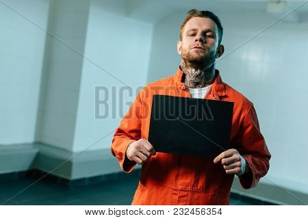 Prisoner Holding Blackboard And Looking At Camera