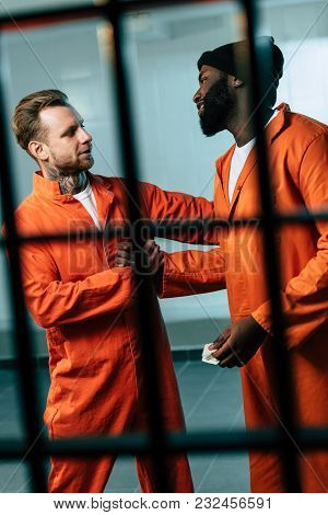 Caucasian Prisoner Buying Drugs At African American Inmate In Prison Cell