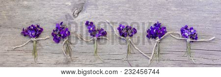 Small Bouquets Of Fragrant Forest Flowers Of Violets Tied With Twine Are Laid Out In A Horizontal Ro