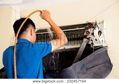 The Young Worker Is Washing Air Condition With Flowing Water To Clean It From Dust And