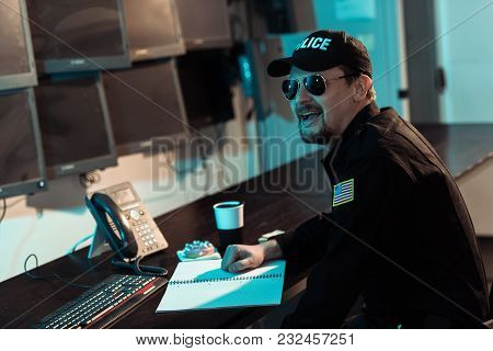Laughing Prison Guard Sitting At Working Table And Monitoring People In Jail