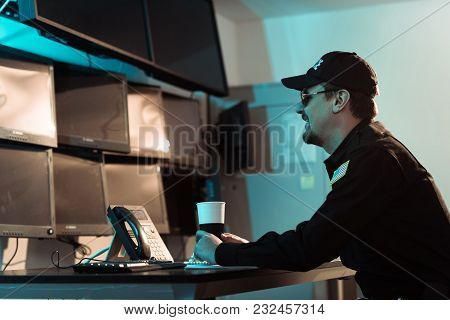 Side View Of Smiling Prison Guard Sitting With Cup Of Coffee And Monitoring People In Jail