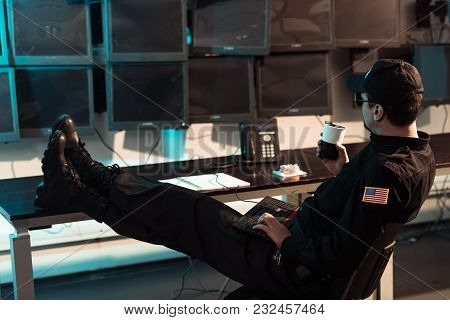 Prison Guard Sitting With Legs On Table And Monitoring People In Jail