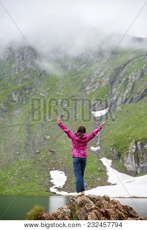 Woman Is Standing With Her Back On A Rock With Her Arms Wide Open And Looks Up Against Background Of