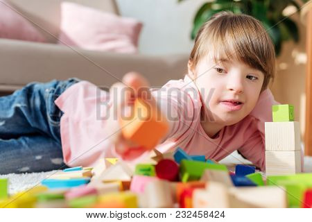 Kid With Down Syndrome Building With Toy Cubes
