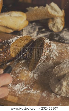 Baker Slices Into Brown Organic Baguette, With Fresh Dough On Cutting Board
