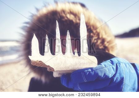 Close Up Picture Of Icicles Held By An Unidentified Hooded Woman On A Beach, Color Toned Picture, Se