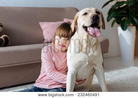 Kid With Down Syndrome Embracing Labrador Retriever