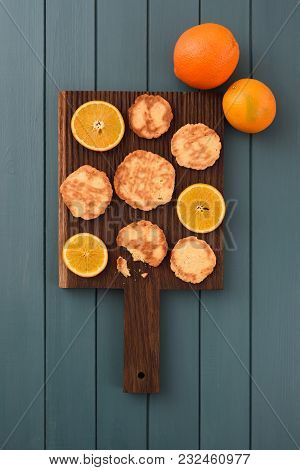 Homemade Imperfect Cookies And Orange Slices On Dark Oak Board Top View Copyspace