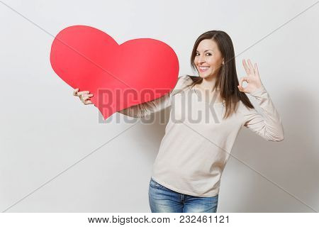 Beautiful Young Smiling Woman Holding Big Red Heart, Showing Ok Gesture On White Background. Copy Sp