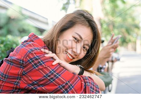 Young Asian Women Sit And Smile Along The Street Enjoying Her City Lifestyle In A Morning Of A Weeke