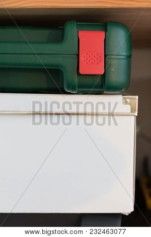 White Cardboard Box And Green Bin For Tools On A Wooden Shelf.