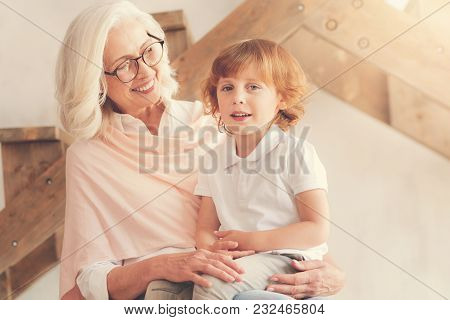 My Kin. Delighted Positive Aged Woman Smiling And Looking At Her Grandson While Holding Him On Her L