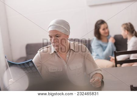 Sick Mature Woman In Kerchief Looking At Mri Scan