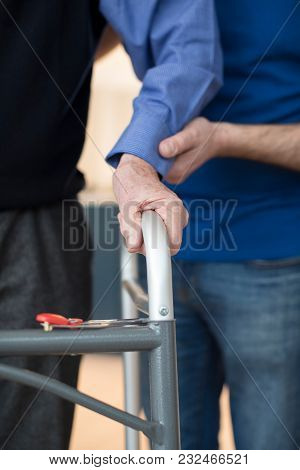 Senior Mans Hands On Walking Frame With Care Worker In Background