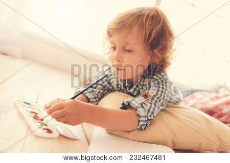 Young Painter. Smart Delighted Creative By Holding A Brush And Putting It Into Paint While Creating