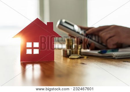 Buying And Selling Houses And Real Estate Prices Concept. Man Using Calculator To Count Rent, Money