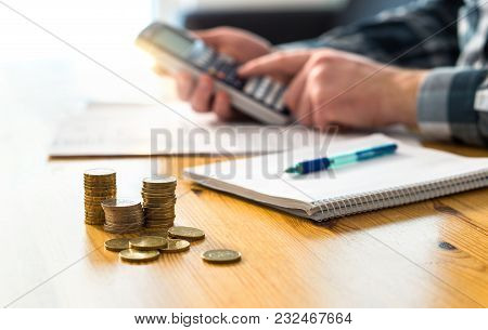 Man Planning Family Finance And Using Calculator. Counting Savings, Budget, Taxes, Expenses And Livi