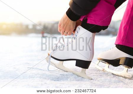 Woman Tying Ice Skates Laces By A Lake Or Pond. Lacing Iceskates. Skater About To Exercise On An Out
