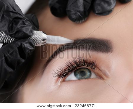 Young woman undergoing procedure of eyebrow permanent makeup in beauty salon, closeup