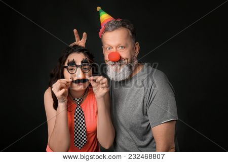 Young woman and mature man in funny disguise on dark background. April fool's day celebration