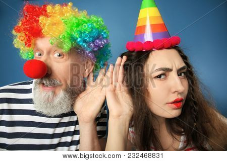 Young woman and mature man in funny disguise on color background. April fool's day celebration