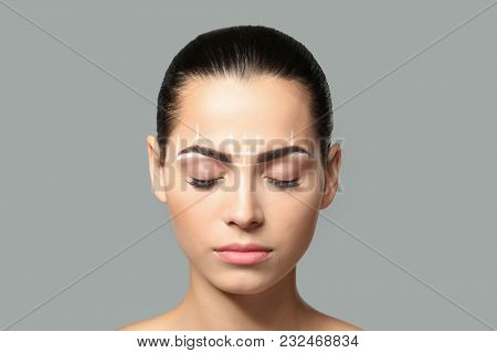 Young woman before procedure of eyebrows permanent makeup on grey background