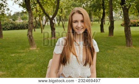 A Young Girl Is Engaged In A Walk In The Park, Looking At A Smart Clock On Her Arm And Receiving A P