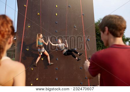 Smiling Girls Giving High Five Hanging On Ropes At Artificial Climbing Wall And Insured By Friends O