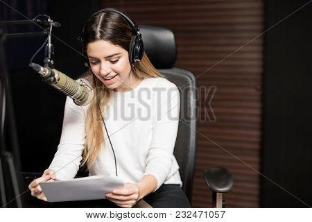 Hispanic Young Female Radio Host Sitting At A Table With Headphones Reading A Script And Broadcastin
