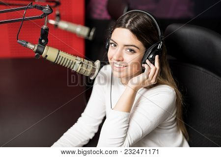 Close Up Of A Beautiful Woman Radio Broadcaster With Headphones Talking In Mic With A Smile On Her F