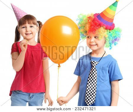 Cute little girl popping brother's balloon with pin on white background. April fool's day celebration