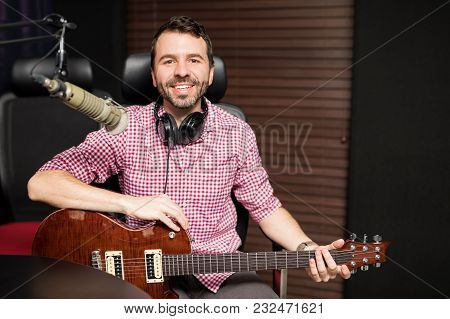 Portrait Of A Good Looking Young Musician And Composer Playing The Guitar At Radio Studio