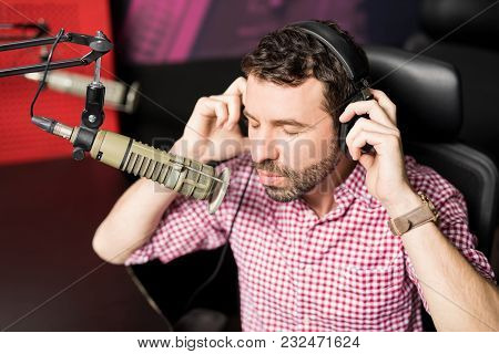 Handsome Young Latin Male Radio Host Adjusting His Headphones While Sitting In Front Of A Microphone
