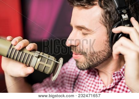 Close Up Of Hispanic Young Man With Headphones Recording A Song With Professional Microphone In Radi