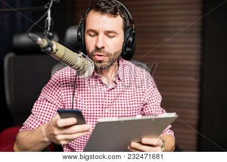 Handsome Young Latin Man Working As Radio Host At Radio Station Sitting In Front Of Microphone Holdi
