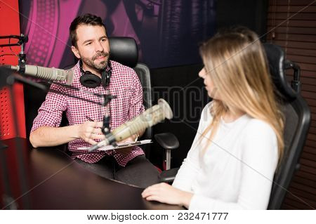 Male Radio Presenter Hosting An Interview With Famous Woman At Radio Station